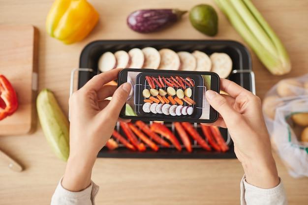 Hoge hoekmening van vrouw met mobiele telefoon en fotograferen van haar bereide schotel van groenten