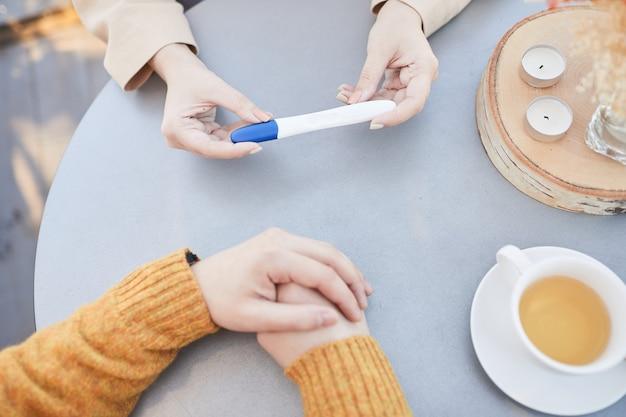 Hoge hoekmening van vrouw zwangerschapstest tonen aan haar man tijdens hun ontbijt aan tafel