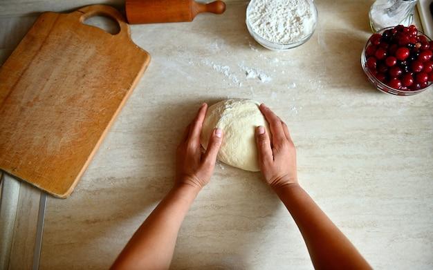 Hoge hoekmening van vrouwelijke handen die deeg kneden op het aanrecht in de keuken, terwijl ze heerlijke traditionele oekraïense dumplings bereiden. proces van het stap voor stap koken van dumplings