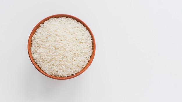 Hoge hoekmening van witte rijst in kom die op witte achtergrond wordt geïsoleerd