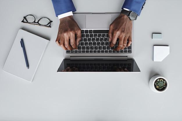 Hoge hoekmening van zakenman typen op laptop die hij online op zijn werkplek communiceert
