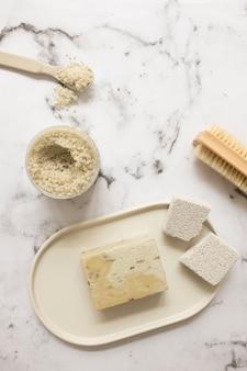 Hoge hoekmening van zeep; zout; puimsteen en penseel op marmer oppervlak