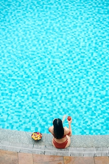 Hoge hoekmening van zwartharige vrouw in zwembroek cocktail drinken en fruit eten terwijl u ontspant
