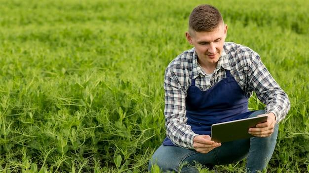 Hoge hoekmens bij landbouwbedrijf met tablet