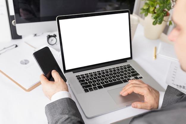Hoge hoekmens die aan laptop werkt