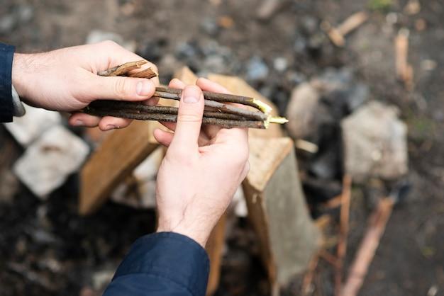 Hoge hoekmens die hout voorbereiden op vuur