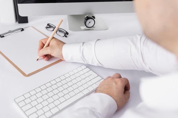Hoge hoekmens die iets op een document schrijft