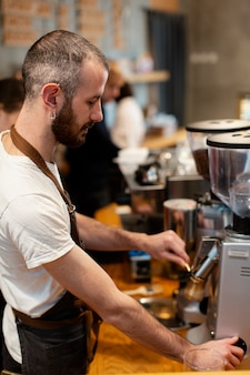 Hoge hoekmens die in koffiewinkel werkt