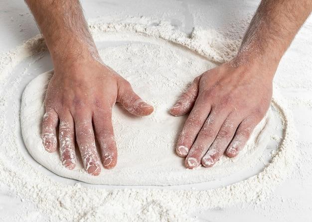 Hoge hoekmens die pizzadeeg kneedt