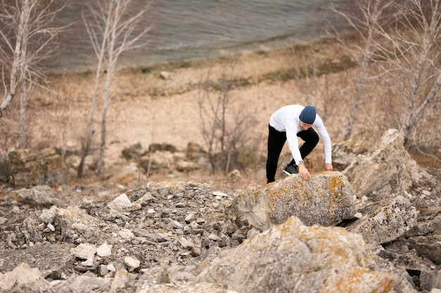 Hoge hoekmens die rotsen in aard beklimt