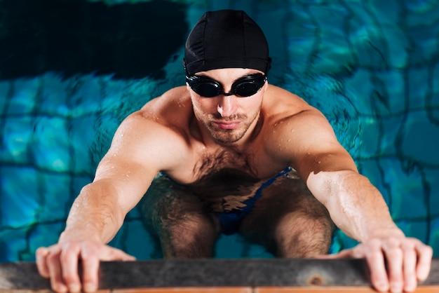 Hoge hoekmens die van zwembad uitgaat
