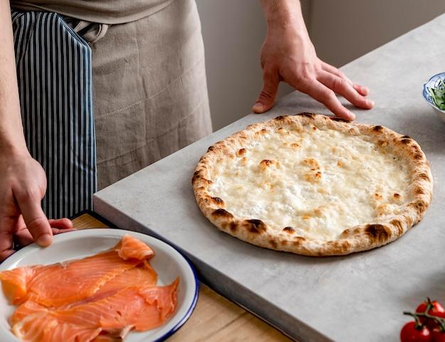 Hoge hoekmens die zich dichtbij gebakken pizzadeeg en gerookte zalmplakken bevindt