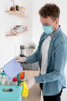 Hoge hoekmens met masker het schoonmaken