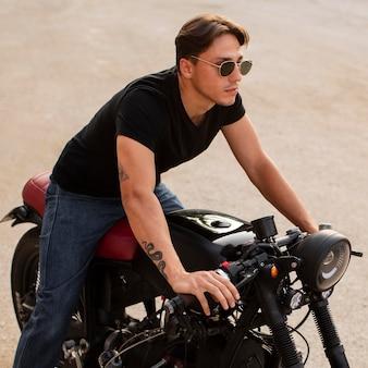 Hoge hoekmens met oude motorfiets