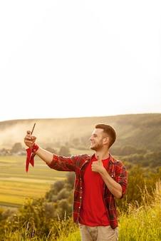 Hoge hoekmens op berg die selfie nemen