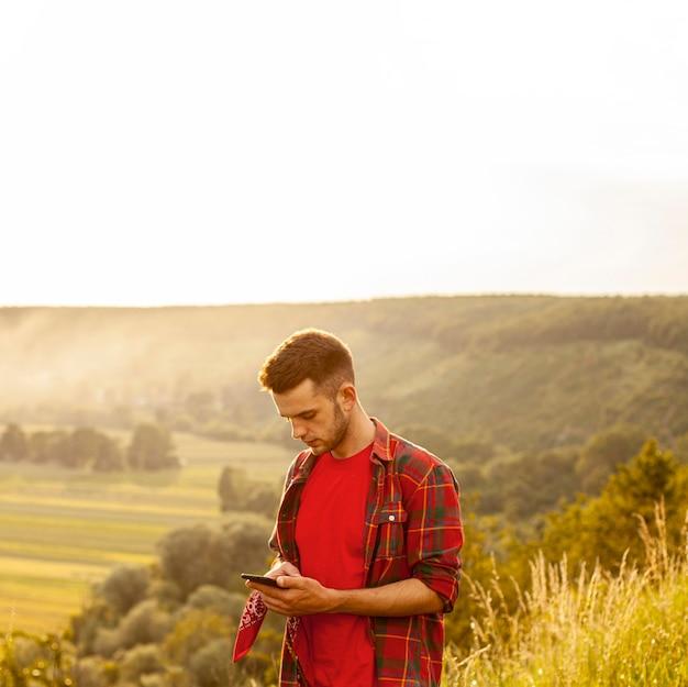 Hoge hoekmens op berg met mobiel
