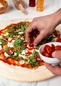 Hoge hoekmens tomaten op pizza zetten