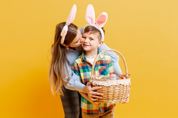 Hoge hoekmoeder en zoon met mand van geschilderde eieren