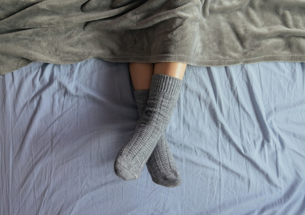 Hoge hoekopname van de benen van een vrouw in grijze gebreide sokken onder de deken