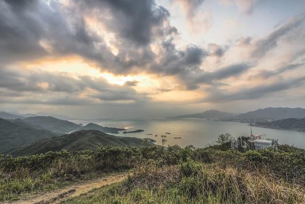 Hoge hoekopname van de met planten bedekte heuvels boven de baai onder de prachtige bewolkte hemel