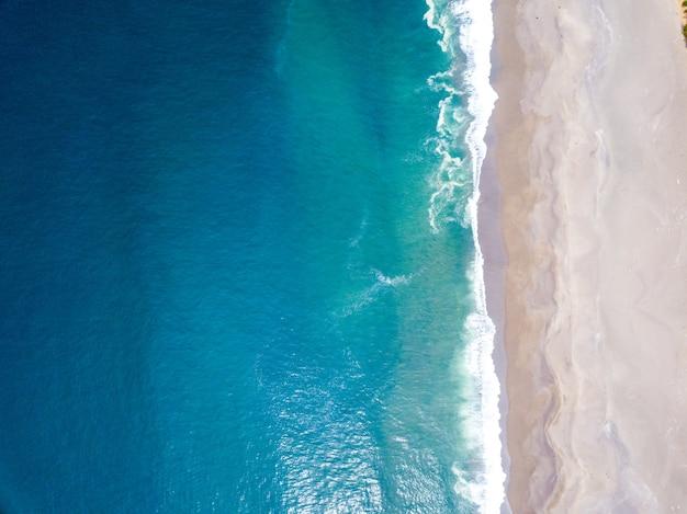 Hoge hoekopname van de oceaangolven die de kust ontmoeten