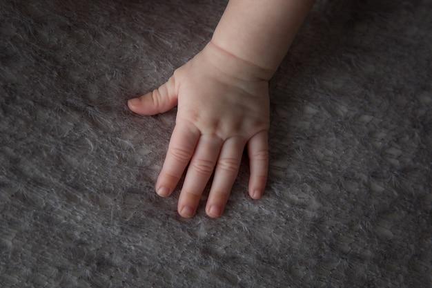 Hoge hoekopname van de zachte en mollige hand van een baby op een pluizige doek