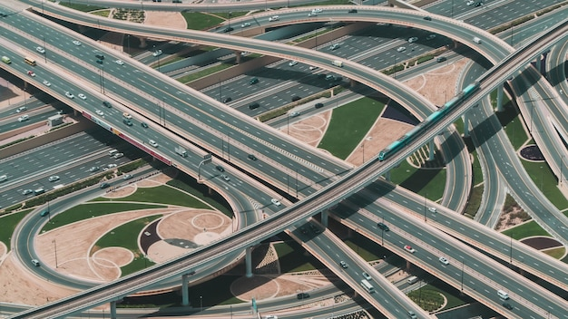 Hoge hoekopname van een grote snelweg met meerdere wegen en een trein die door de centrale weg rijdt