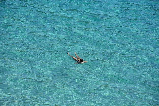 Hoge hoekopname van een man die in het water aan het zonnebaden is