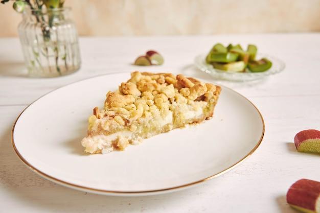 Hoge hoekopname van een plakje knapperige rhabarbar-taarttaart met wat ingrediënten op een tafel