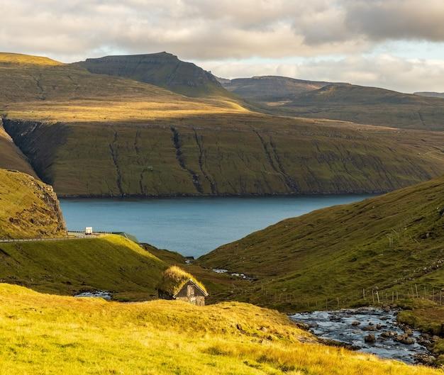 Hoge hoekopname van een prachtig meer omringd door groene bergen onder een bewolkte hemel