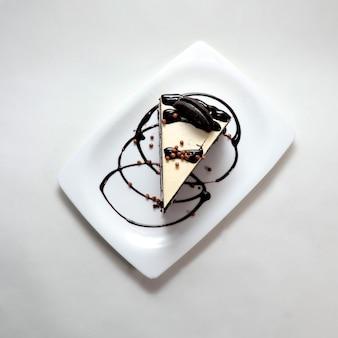Hoge hoekopname van een stuk romige cheesecake met chocoladekoekjes