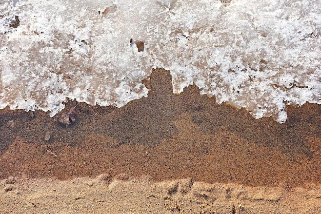 Hoge hoekopname van een zandstrand en bevroren water