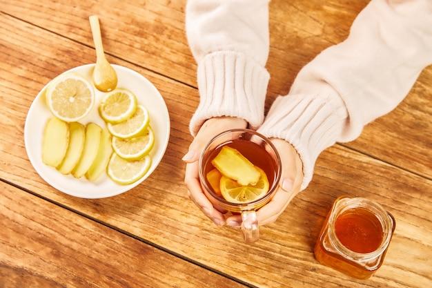 Hoge hoekopname van handen met een kopje thee met citroenen, gember en honing op tafel