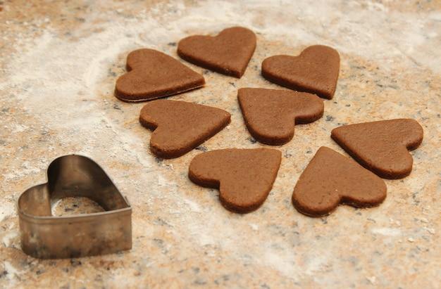 Hoge hoekopname van hartvormige koekjes naast een hartvormige koekjesvorm