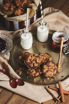 Hoge hoekopname van heerlijke kerstkoekjesmuffins op een bord met honing en melk