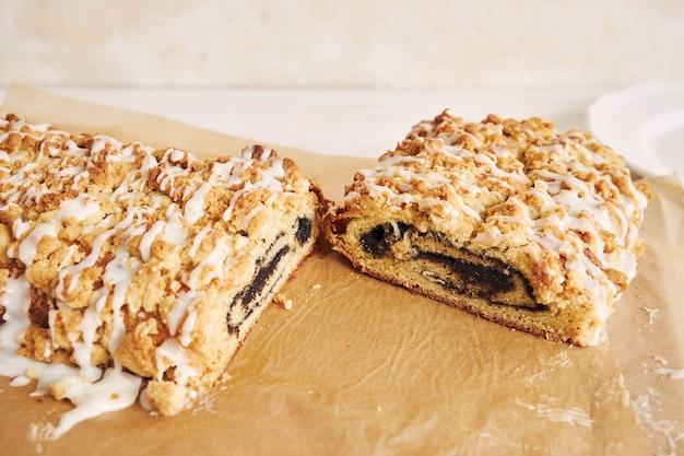 Hoge hoekopname van heerlijke maanzaadcake met een witte suikerglazuur op een witte tafel