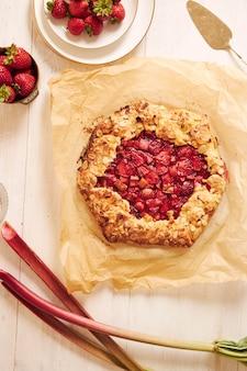 Hoge hoekopname van heerlijke rabarber-aardbeien-gallaatcake met ingrediënten op een witte tafel