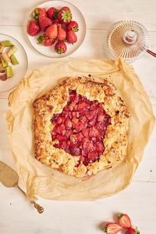Hoge hoekopname van heerlijke rabarber- en aardbeiencake met ingrediënten op een witte tafel
