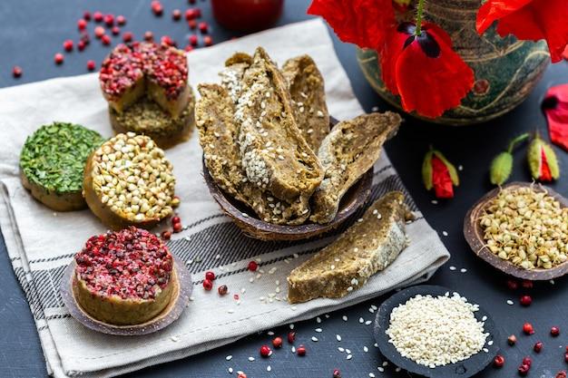 Hoge hoekopname van rauw veganistisch brood met rode peper, boekweit, klaprozen op een donker tafelblad
