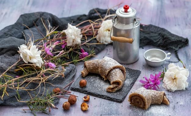 Hoge hoekopname van rauwe veganistische broodjes, hazelnoten, een aluminium melkfles en witte en roze bloemen