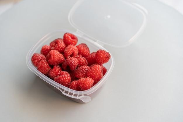 Hoge hoekopname van verse frambozen in een plastic doos op een wit oppervlak