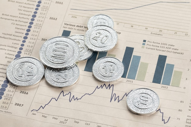 Hoge hoekopname van zilveren munten op pagina's met staafdiagrammen