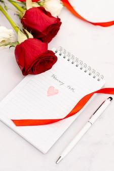 Hoge hoekopstelling met rozen en notitieblok