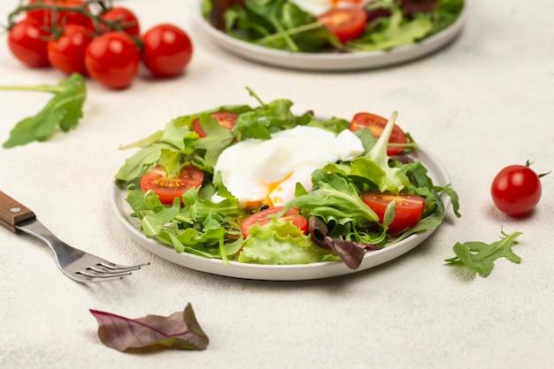 Hoge hoeksalade met tomaten en gebakken ei