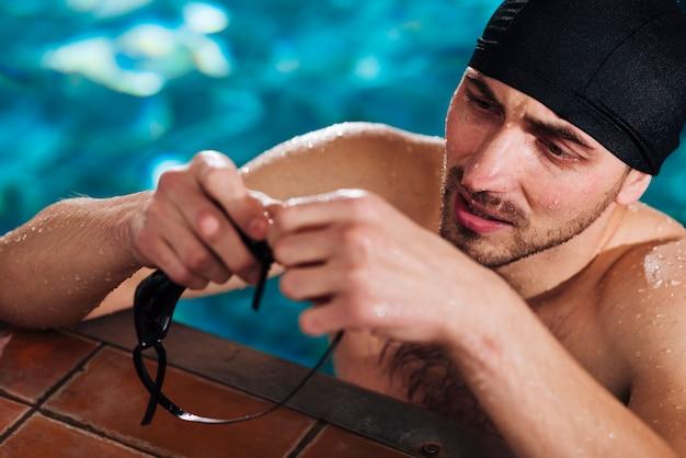 Hoge hoeksportman die zwembril voorbereiden