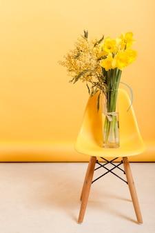 Hoge hoekstoel met vaas met bloemen