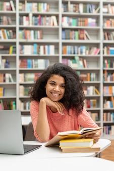 Hoge hoektiener die bij bibliotheek bestudeert