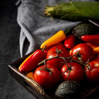 Hoge hoektomaten, avocado's en paprika's in lade