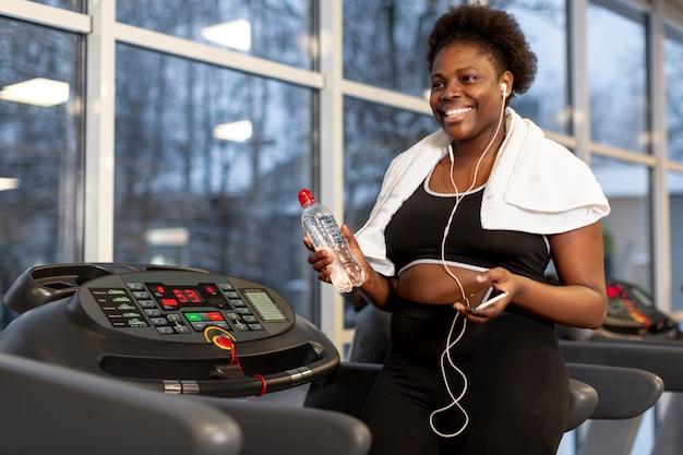 Hoge hoekvrouw bij gymnastiek mobiel gebruiken