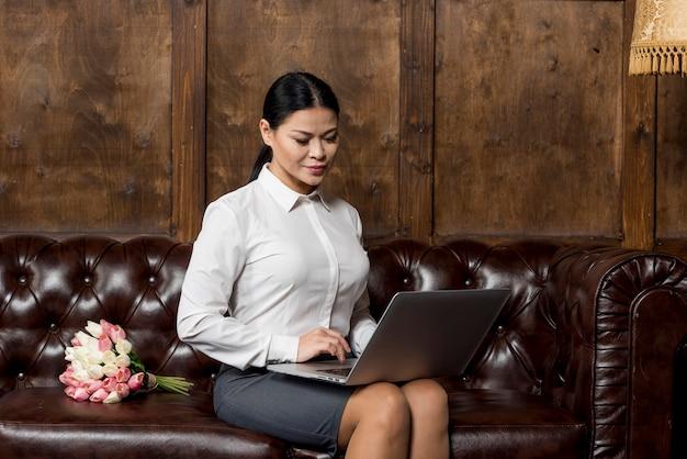 Hoge hoekvrouw die aan laptop werkt